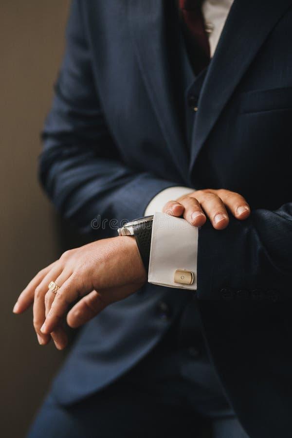 Un homme dans un costume élégant bleu regarde sa montre Mains en gros plan avec des manteds et des boutons de manchette d'or photos stock