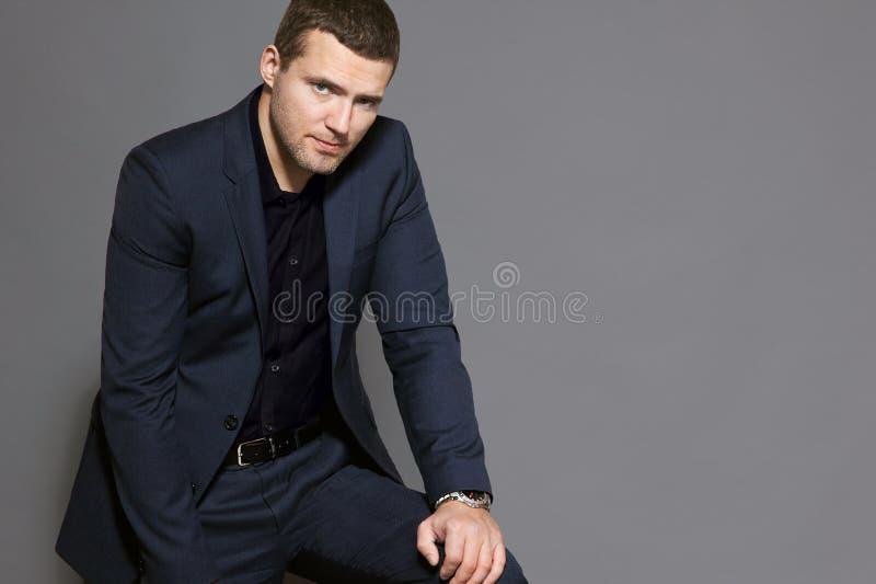 Un homme dans un costume bleu s'assied sur un studio gris de fond photo libre de droits
