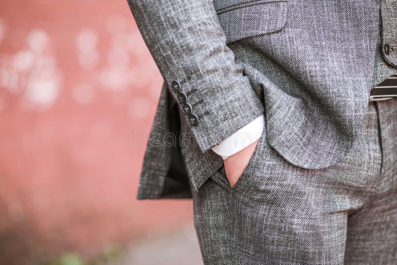 Un homme dans un costume a mis sa main dans sa poche image libre de droits