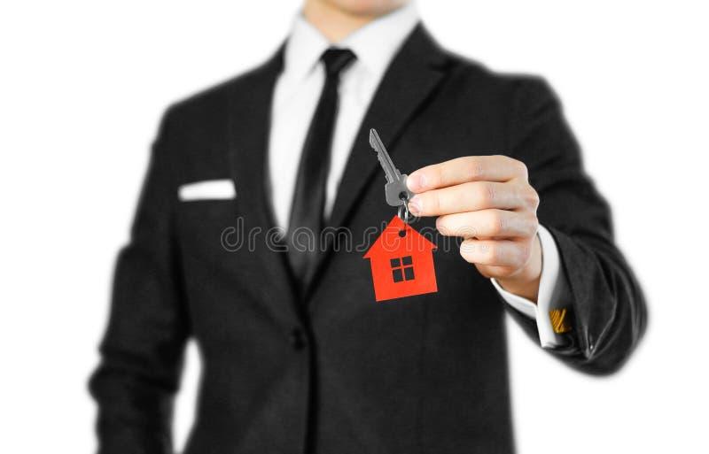 Un homme dans un costume noir tient les clés sur la maison Rouge de porte-clés image stock