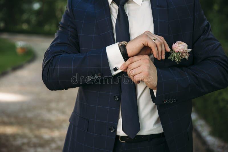 Un homme dans un costume, plan rapproché blanc de chemise d'un cadre cultivé L'homme d'affaires met dessus des boutons de manchet photographie stock