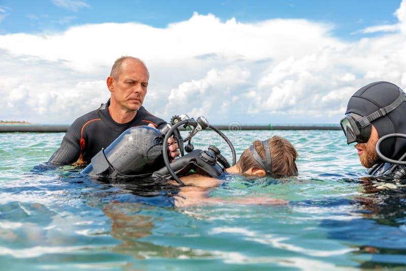 Un homme dans un costume pour plonger dispose un garçon à plonger images stock