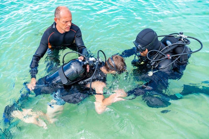 Un homme dans un costume pour plonger dispose un garçon à plonger image stock