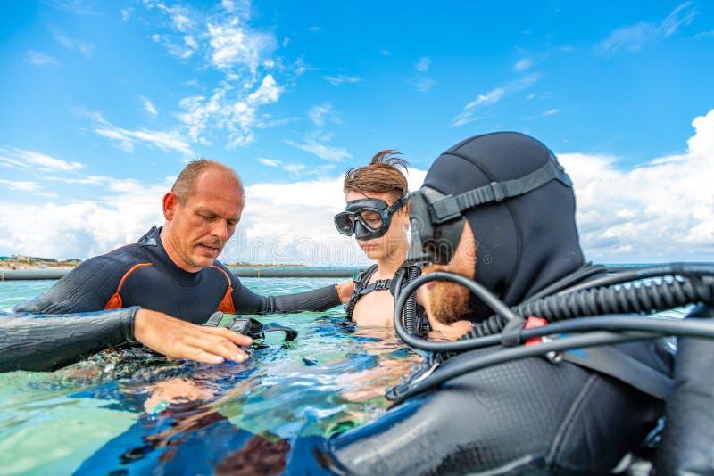 Un homme dans un costume pour plonger dispose un garçon à plonger image libre de droits
