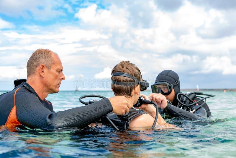 Un homme dans un costume pour plonger dispose un garçon à plonger photos stock