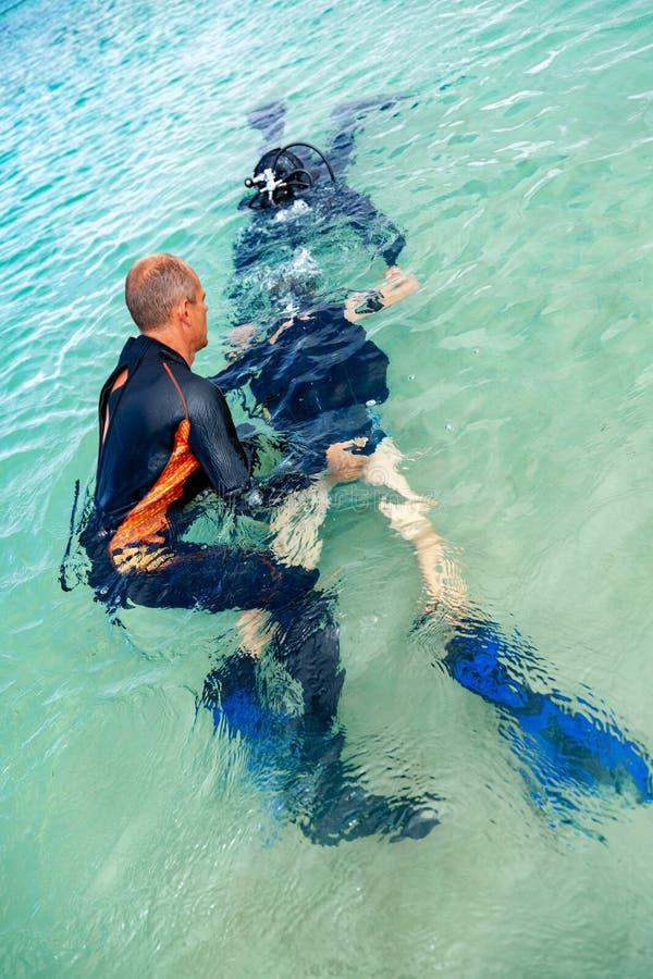Un homme dans un costume pour plonger dispose un garçon à plonger photo stock