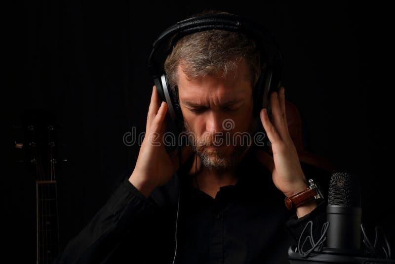 Un homme dans des écouteurs écoutant la musique sur un fond foncé photos stock