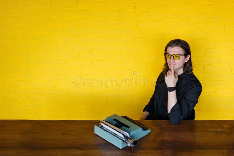 Un homme dans des lunettes jaunes, posées sur une table en bois près de la machine à écrire, pensant, endroit pour un texte photos stock