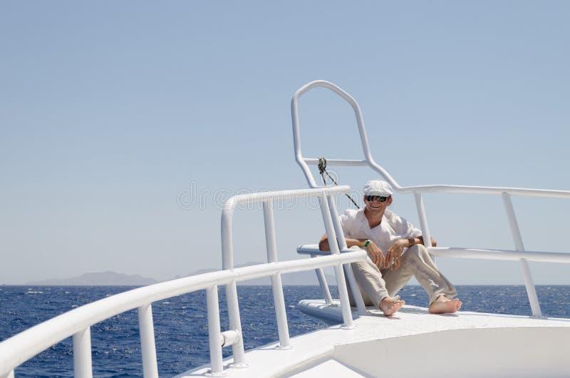 Un homme dans des vêtements lumineux portant un chapeau et des lunettes sur un yacht photo stock