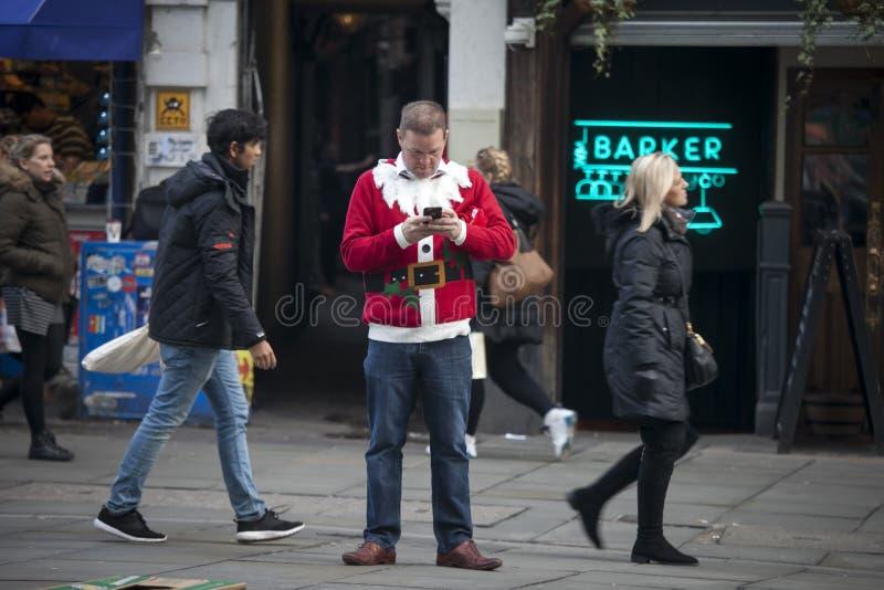 Un homme dans le costume de Santa Claus se tient au milieu du trottoir et écrit au téléphone photo libre de droits