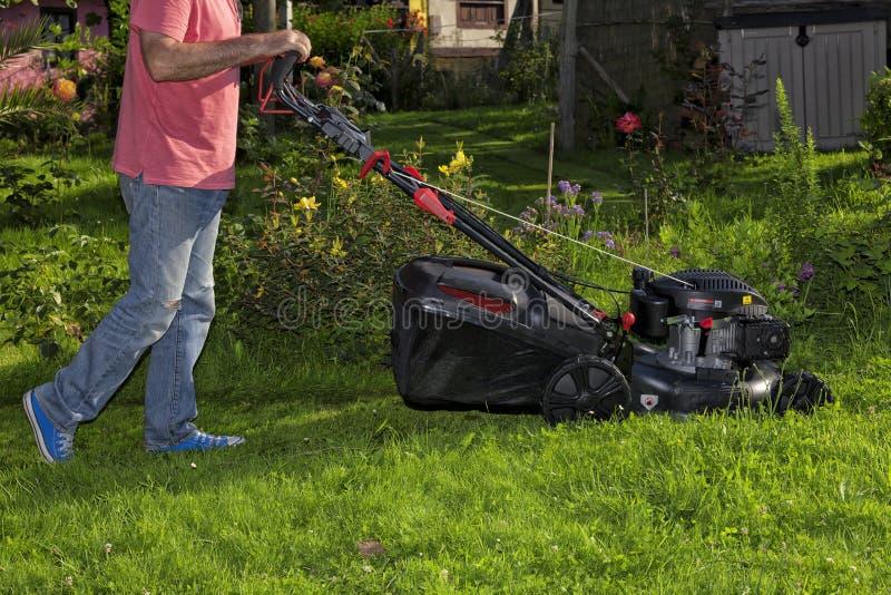 Un homme dans le jardin coupe l'herbe avec une faucheuse photo libre de droits