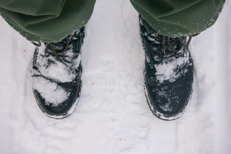Un homme dans les bottes couvertes de neige se tient sur un chemin forestier Un fragment du pied, plan rapproché photo stock