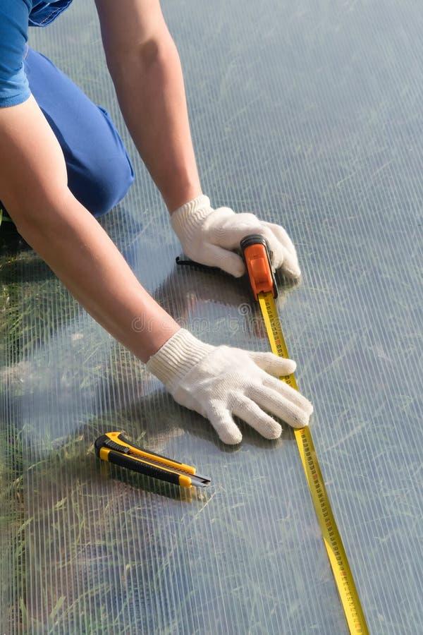 Un homme dans les gants blancs fait des mesures du plastique transparent utilisant un ruban métrique photos libres de droits