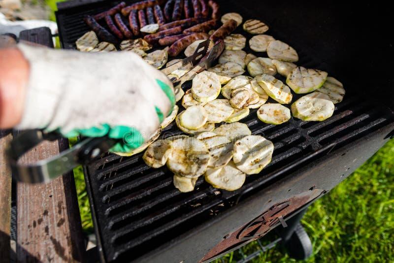 Un homme dans les gants fait cuire des saucisses et des légumes grillés Barbecue d'?t? photo libre de droits