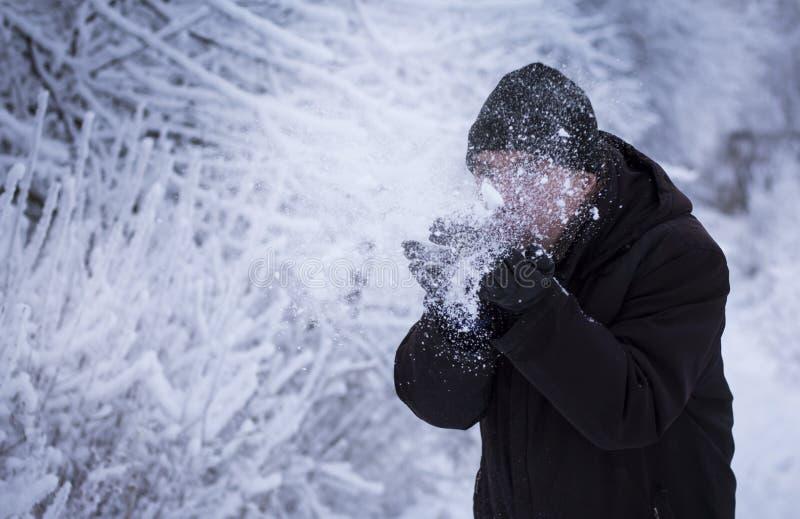 Un homme dans un paysage neigeux soufflant sur la neige dans des ses mains images stock