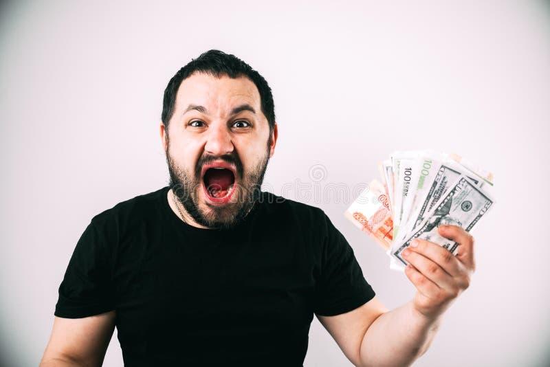 Un homme dans un T-shirt noir crie et montre son prix d'argent liquide dans d'euro dollars et roubles photographie stock libre de droits