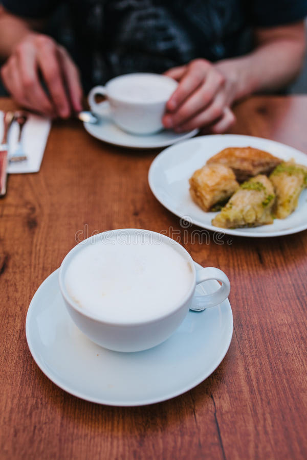 Un homme dans un café mange du café avec un dessert oriental traditionnel de baklava Nourriture orientale Dessert turc Nourriture photographie stock