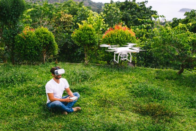 Un homme dans un casque de réalité virtuelle se reposant à côté du bourdon photos libres de droits