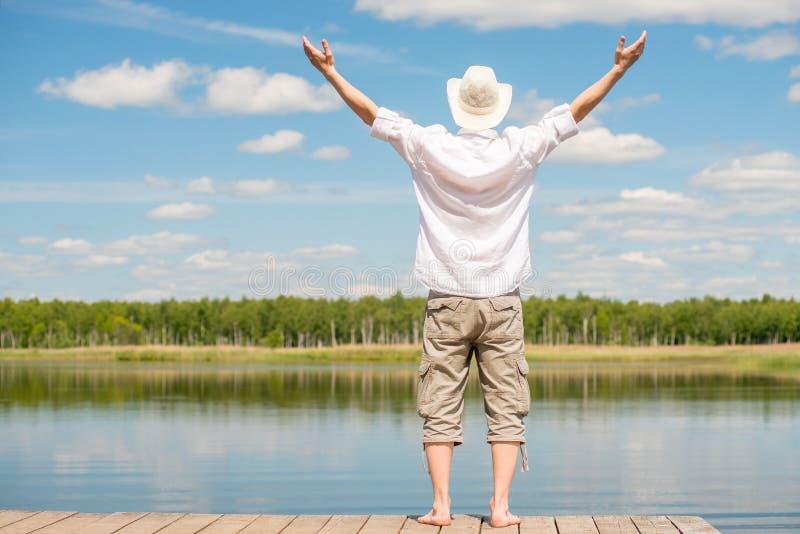 Un homme dans une chemise blanche avec des bras a étendu dans l'enjoyin de côtés photographie stock libre de droits