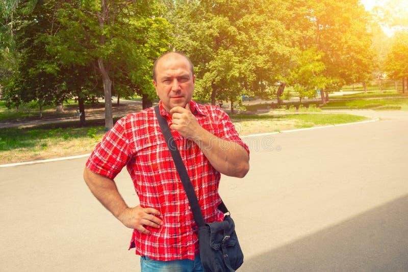 Un homme dans une chemise rouge et un sac noir se tient en parc contre le contexte du soleil et tient sa tête avec sa main photo stock