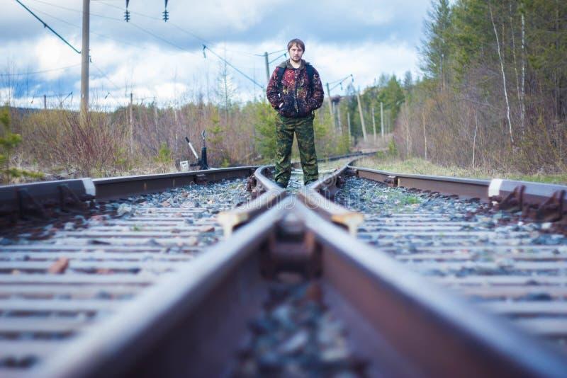 Un homme dans une tenue de protection se tient à l'intersection des chemins de fer images libres de droits