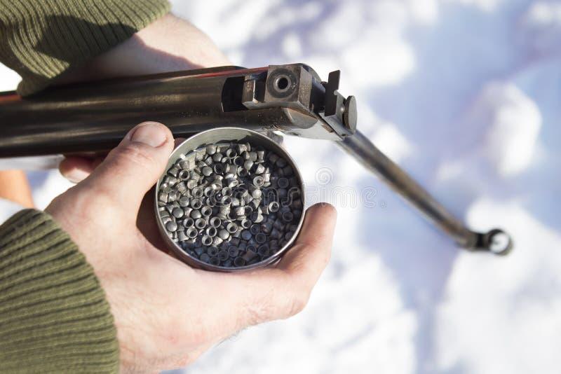 Un homme dans une veste de camouflage tenant une arme à feu de BB et une boîte de chevrotine, munitions image stock