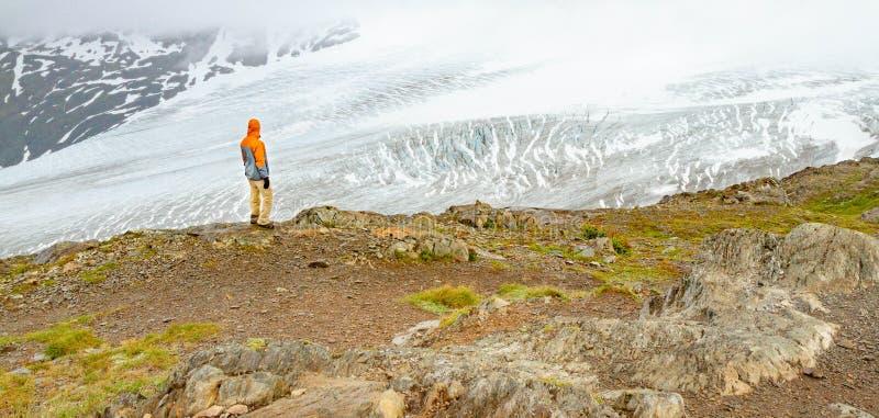 Un homme dans une veste orange regarde fixement au-dessus du glacier de sortie en Alaska, Etats-Unis photographie stock