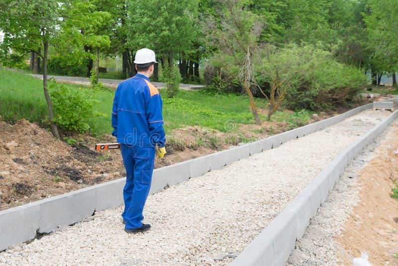Un homme dans un uniforme bleu est tenant et regardant une route non finie photo stock
