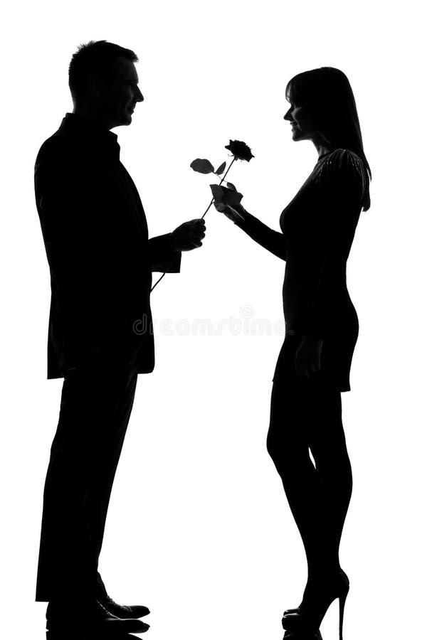Un homme de couples offrant la fleur et la femme roses photos stock