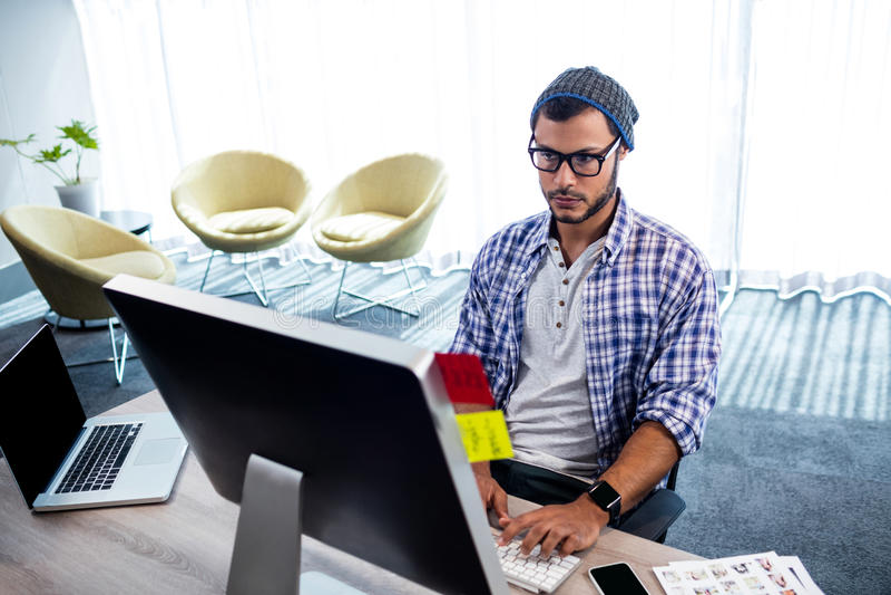 Un homme de hippie travaillant au bureau d'ordinateur photographie stock
