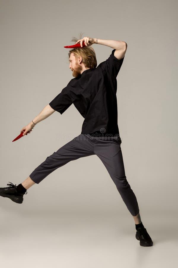 Un homme de ninja dans l'usage noir avec deux poivrons de piments rouges dans des ses mains images libres de droits