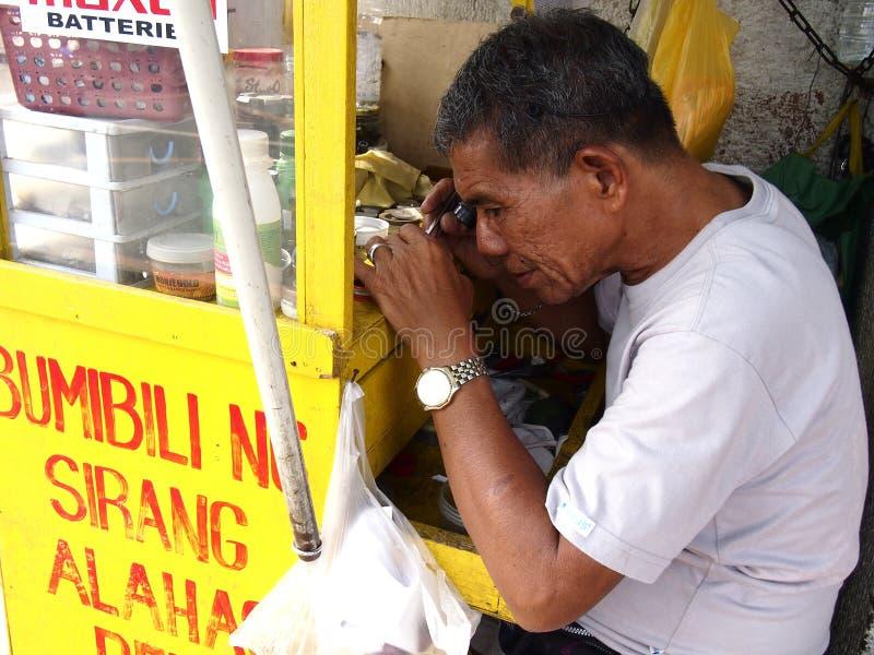 Un homme de réparation de montre travaille à une montre dans sa stalle image stock