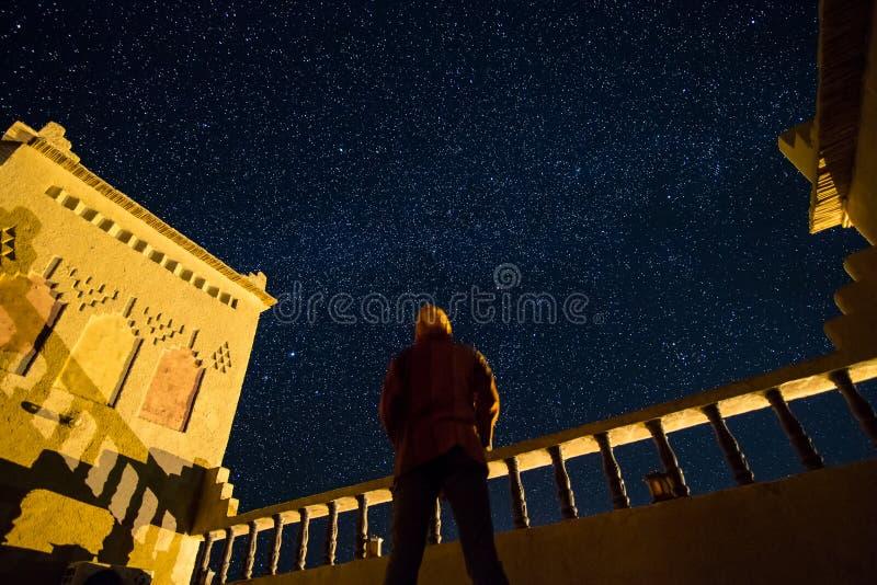 Un homme debout regardant le ciel étoilé sur le toit d'un kasbah au Maroc du sud photo libre de droits
