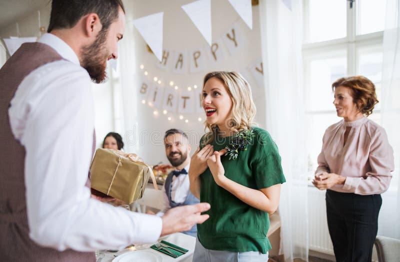 Un homme donnant le cadeau à une jeune femme étonnée sur une fête d'anniversaire de famille photos libres de droits
