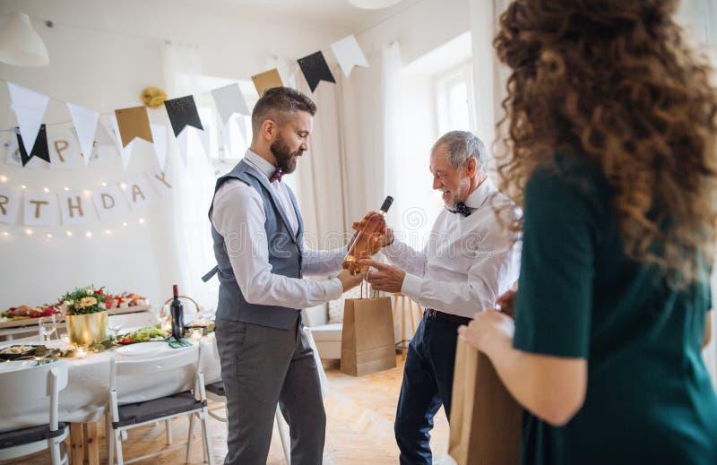 Un homme donnant une bouteille de vin à son père sur la fête d'anniversaire d'intérieur, un concept de célébration images stock