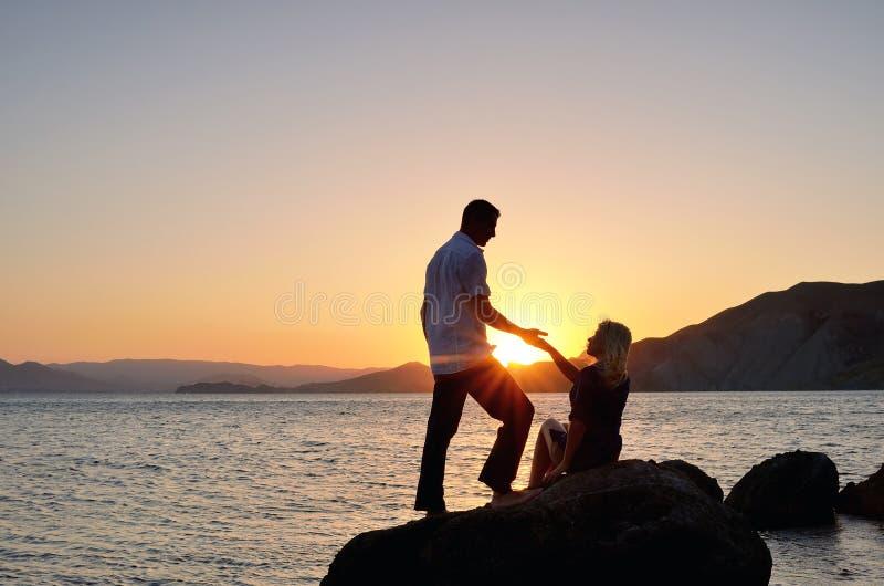 Un homme donne la main d'un femme sur la plage photo libre de droits