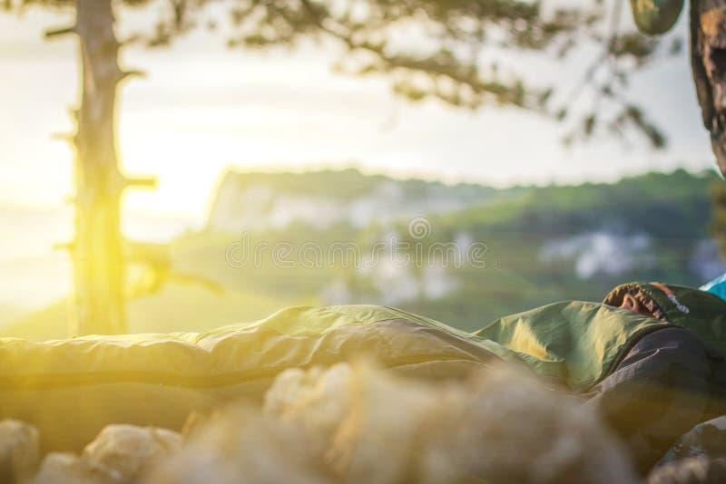 Un homme dormant dans le sac de couchage photographie stock
