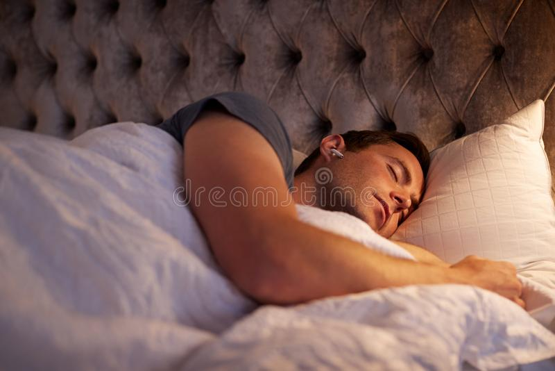 Un Homme Dormant Dans Un Lit Portant Des Écouteurs Sans Fil Connectés À Un Téléphone Mobile image stock