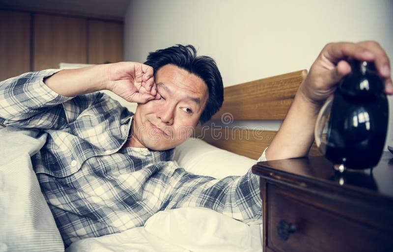 Un homme dormant solidement se réveillant de l'alarme photos libres de droits