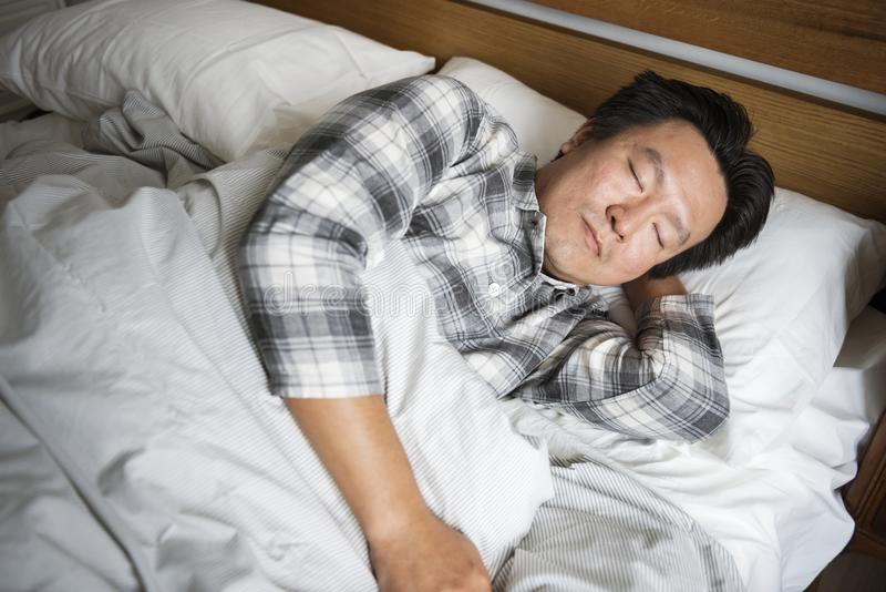 Un homme dormant solidement sur le lit image stock