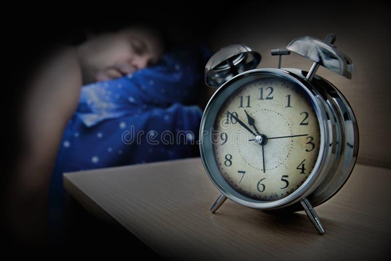 Un homme dormant sur le lit près du réveil photo libre de droits