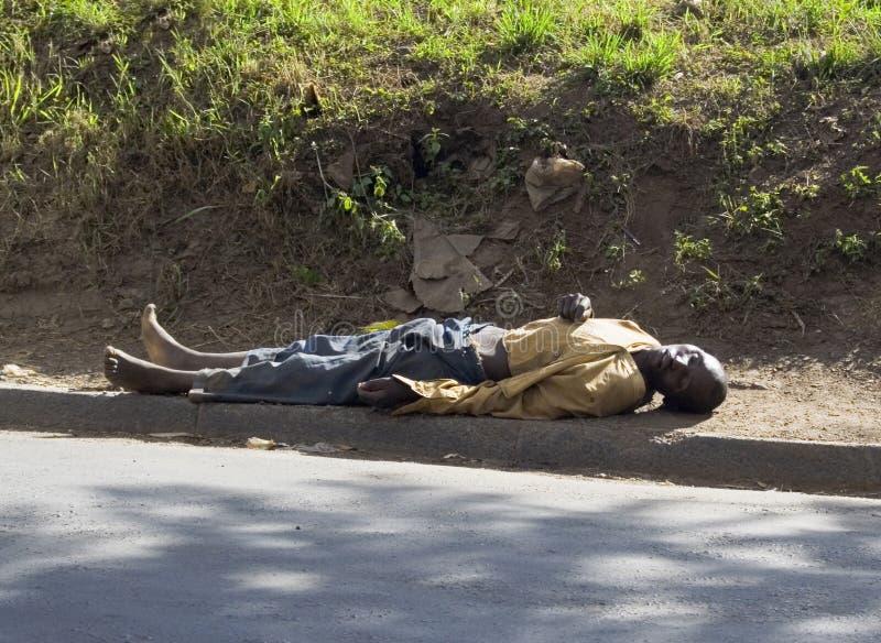 L'homme sans abri dort sur la rue images stock