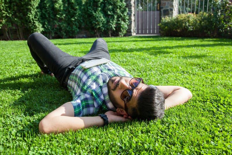 Un homme du Moyen-Orient de mode avec la barbe, coiffure de mode se repose le beau temps de jour d'herbe verte photo stock