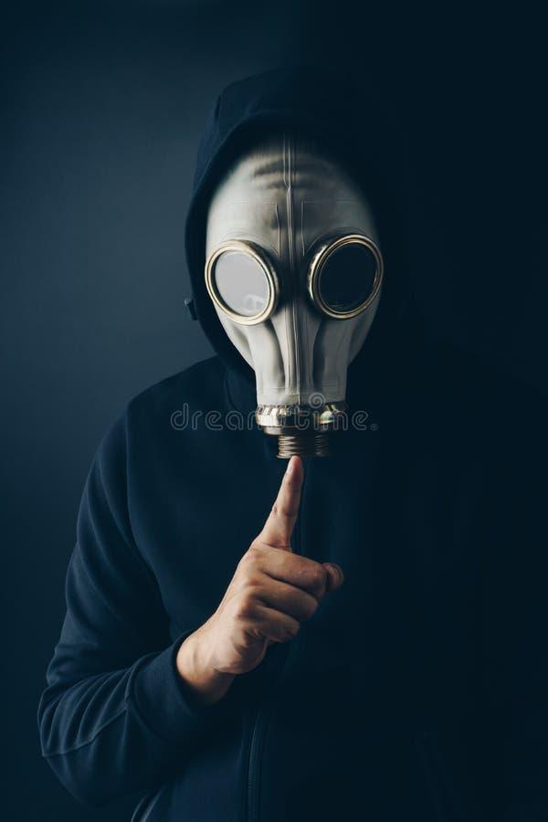 Un homme effrayant dans le masque de gaz faisant le geste de silence images libres de droits