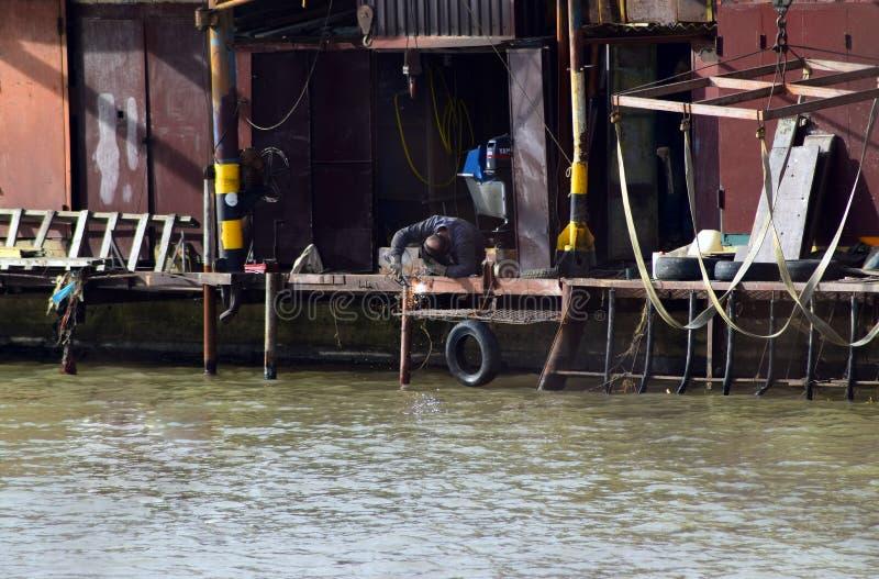 Un homme emploie la soudure dans son exploitation de pisciculture image stock