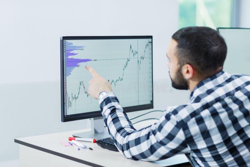 Un homme employant le logiciel pour gérer des projets sur un ordinateur portable image stock