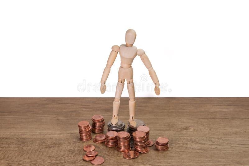 Un homme en bois de poupée avec son épargne, pièce d'or Tous ont composé avec le cent vingt-cinq cent, cinquante de baht thaïland photos stock