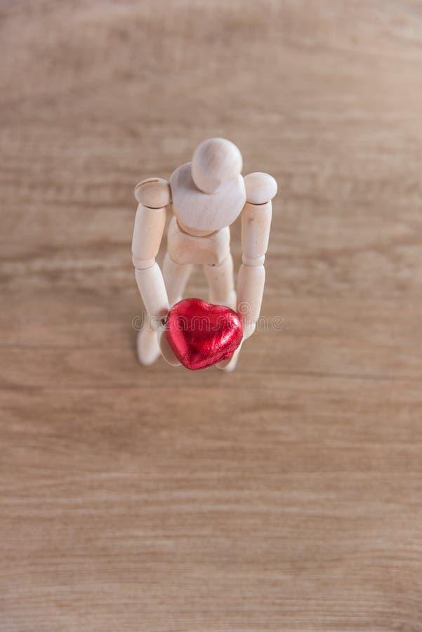 Un homme en bois de poupée dans le Saint Valentin Représentation de l'amour sur le plancher en bois avec la chaleur image libre de droits