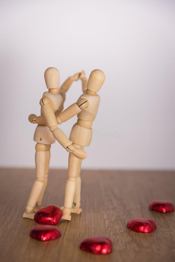Un homme en bois de poupée dans le Saint Valentin Représentation de l'amour sur le plancher en bois avec la chaleur photos stock