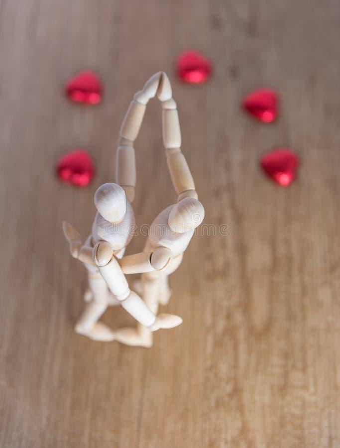 Un homme en bois de poupée le Saint Valentin sur le plancher en bois avec l'acte de l'amour et de la relation image libre de droits
